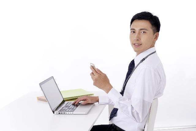 ノートパソコンを前にスマートフォンを持つ男性
