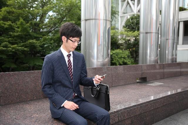 屋外でスマートフォンを見る男性