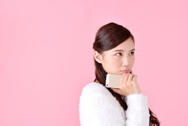 スマートフォンを持って悩む女性