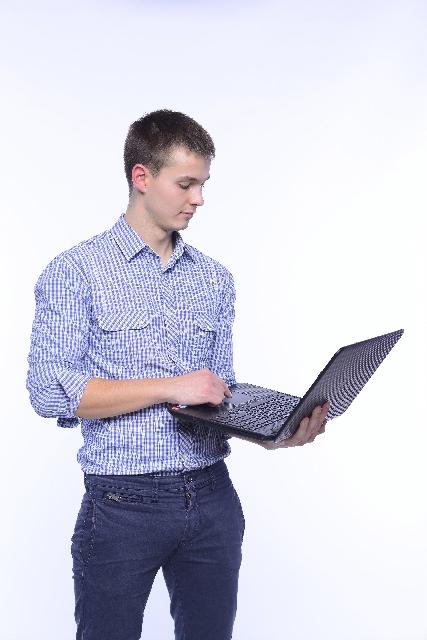 ノートパソコンを持つラフな格好の男性