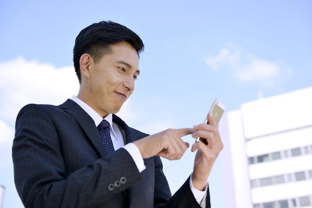 街中でスマートフォンをチェックする男性
