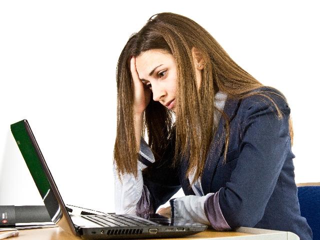 ノートパソコンの前で考える女性